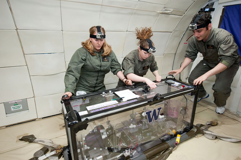 The UW team's experiment included a spinning drum, on the left, that fed liquid through a series of sensors before emptying into the bucket on the right. All equipment had to be enclosed and secured to the floor for safety. Even the notebook and pen are taped down so they won't float away in zero gravity.
