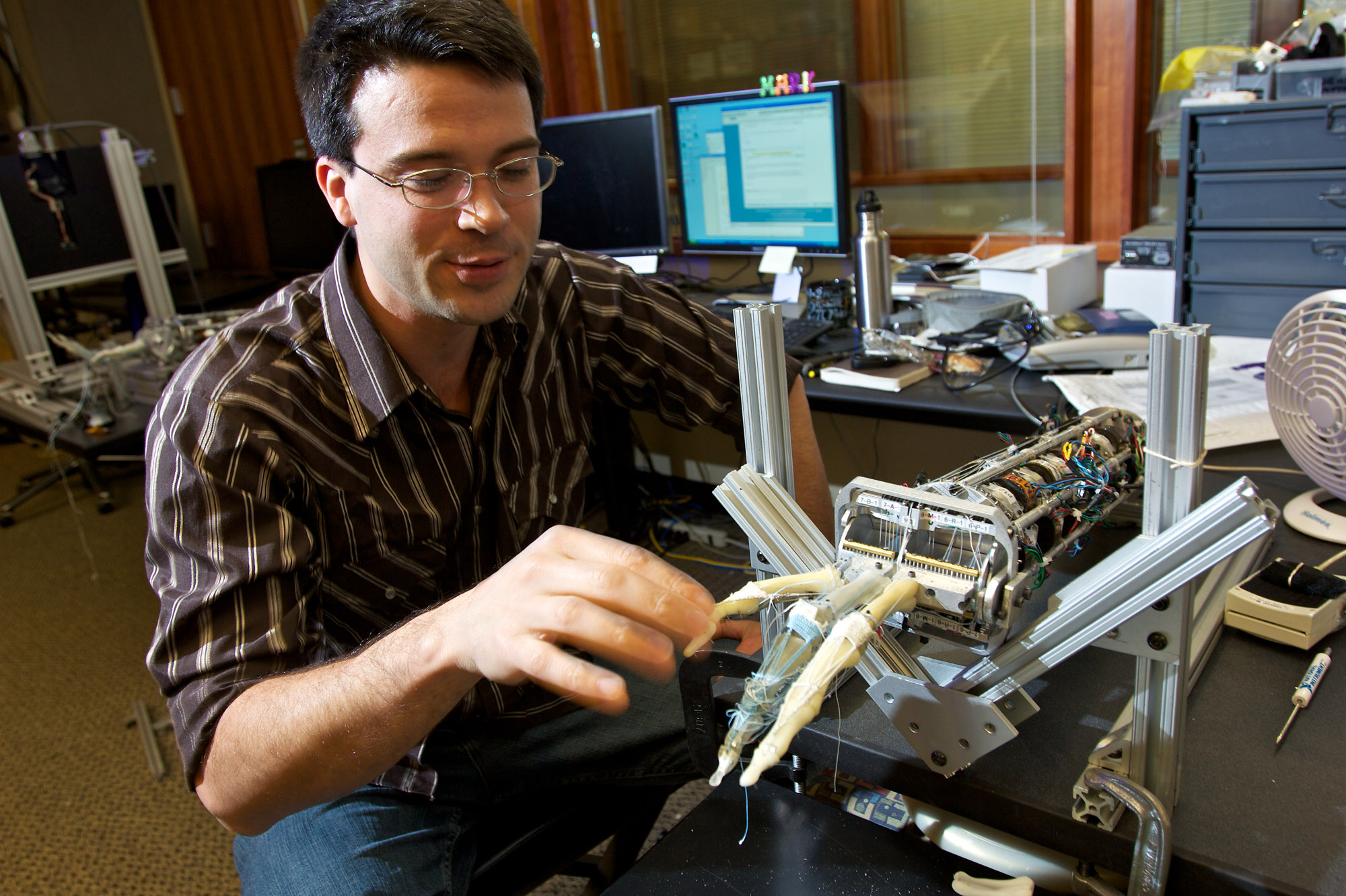 UW doctoral student Eric Rombokas with a prototype prosthesis built in the Neurobotics Lab.