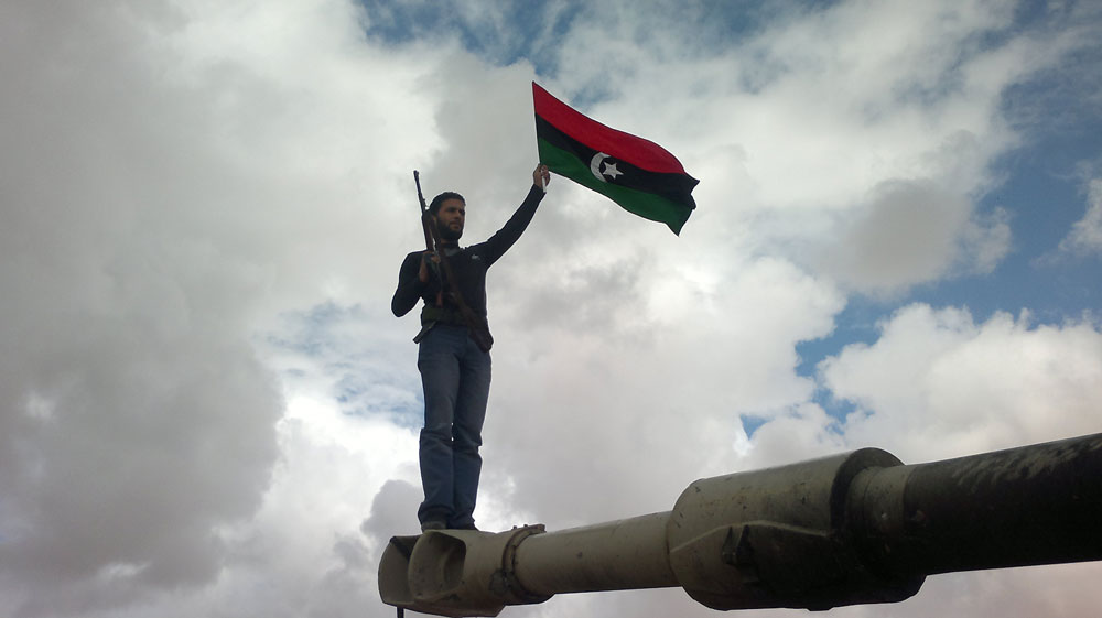 A rebel waves a Libyan flag while standing atop a tank gun.