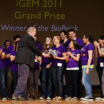 "Liz Stanley, a senior majoring in microbiology, accepts the brick trophy on a Boston stage Nov. 7 for the iGEM team's ""World Champion"" win in genetic engineering. The brick is a symbol of the molecular components that are used in synthetic biology."