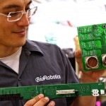 UW electrical engineering doctoral student Hawkeye King holds the circuit boards and connectors for the Raven II robot.