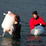 Christian Frazar and David Schruth collect water samples from Puget Sound near Seattle.