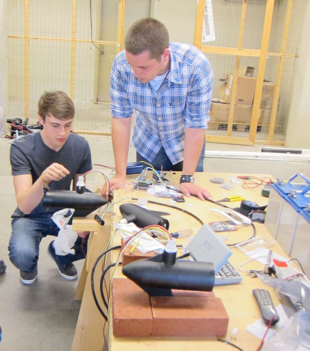 Taylor Juve and Trevor Uptain work on the robots thruster motors.