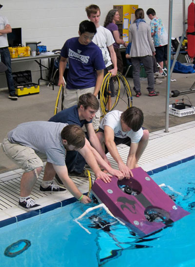 UW students Tysen Mulder, Taylor Juve, Scott Daley (left to right, crouching), Brian auf der Springe and Ryan Cox (standing behind) launch the robot during a recent regional competition.