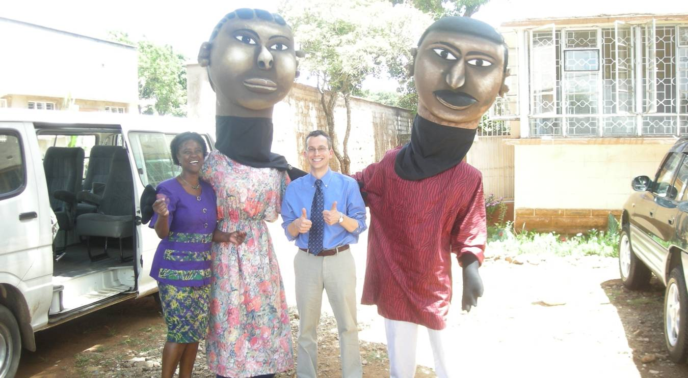 The Thika, Kenya puppets used in public education programs to recruit couples to the HIV prevention study, pose with researchers Dr. Nelly Mugo and Dr. Jared Baeten.