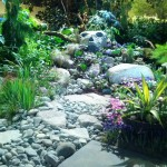 Plants, stone walkway and face of stone in garden