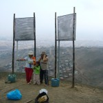 Three community members stand at base ofosts with rectangular screens to collect fog on hill over city
