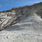 Large cliff of white ashy material surrounded by rock cliffs when two researchers working the face