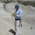 Researcher holds GPS unit in hand standing on field of ash during sampling
