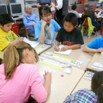 Four elementary students work at desk with UW undergraduate