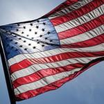 Sun shining through the U.S. flag, with a UW logo.