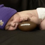 Baby asleep wearing purple cap and holding tiny football