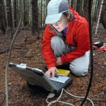 Susan Dickerson-Lange downloads data onto her laptop from a weather station located in dense, second-growth forest in the Cedar River Watershed.
