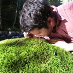 Students uses hand lens to examine moss on rock