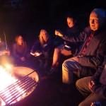 Students and professor around campfire