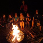 Students seated around campfire