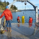 people on boat deploying instrument