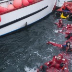 Six swimmers in survival suits float in a row in water