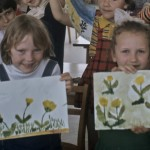 Two girls hold up similar drawings of flowers