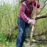 Woman uses shovel to dig