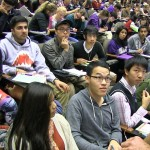 Man talks with two rows of students in class auditorium
