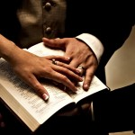 Hands of a man and woman wearing weddng rings on to pf open bible