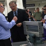 Gov. Jay Inslee learns about riveting from Boeing engineer Riley Hanson Smith, left, and Sai Krovvidi, a UW doctoral student in mechanical engineering, at the opening of the Boeing Advanced Research Center on campus.