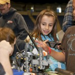 A young girl takes notice of a robot project at a college event promoting science to children.