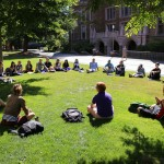 A University of Washington class meets outside of Mary Gates Hall on a sunny day. Photo of students in a circle under a tree.