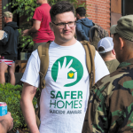 Forefront Program Coordinator Brett Bass joins fellow veterans to build awareness about the Save Homes, Suicide Aware program. Photo of Brett talking to two veterans.