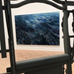 """Spoiled Landscapes - Ocean,"" an oil on canvas by Baorong Liang is seen through a gap in Brighton McCormack's house-like structure ""Fully Furnished"" (in video above) at the 2019 MFA + MDes Thesis Exhibition at the Henry Art Gallery."