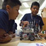 Two fifth-grade boys from Forks, WA point out design elements of their LEGO lunar rover.
