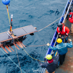 researchers on ship lowering large surfboard into water