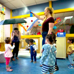 Toddlers stand in a circle, clapping. Adults stand nearby.