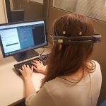 Woman working on computer, wearing headset while