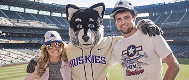 Harry Husky the mascot pictured with two fans.
