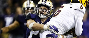 Husky football player Ben Burr-Kirven tackles an ASU player.