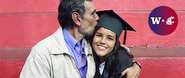 young woman in graduation cap and gown being kissed on the head by a fatherly looking man