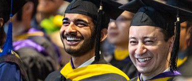 two men in graduation caps and gowns during crowded GIX graduation ceremony 2018