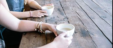 Two people sit at a wooden table with coffee cups.