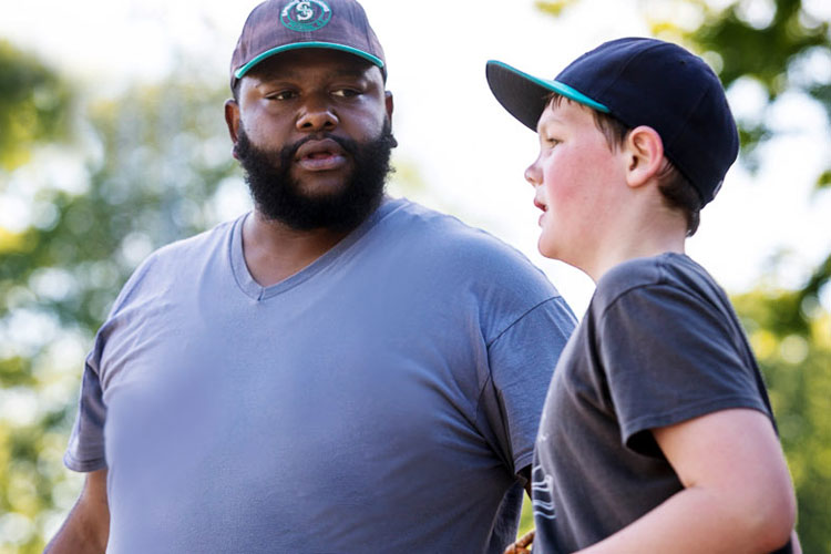 Baseball coach talks to player.