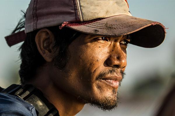 Cambodian fisherman gazing into the sun