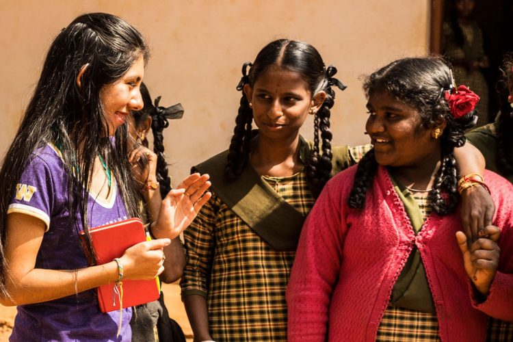 Cristina Lopez standing outside with a group of Indian schoolgirls in uniform