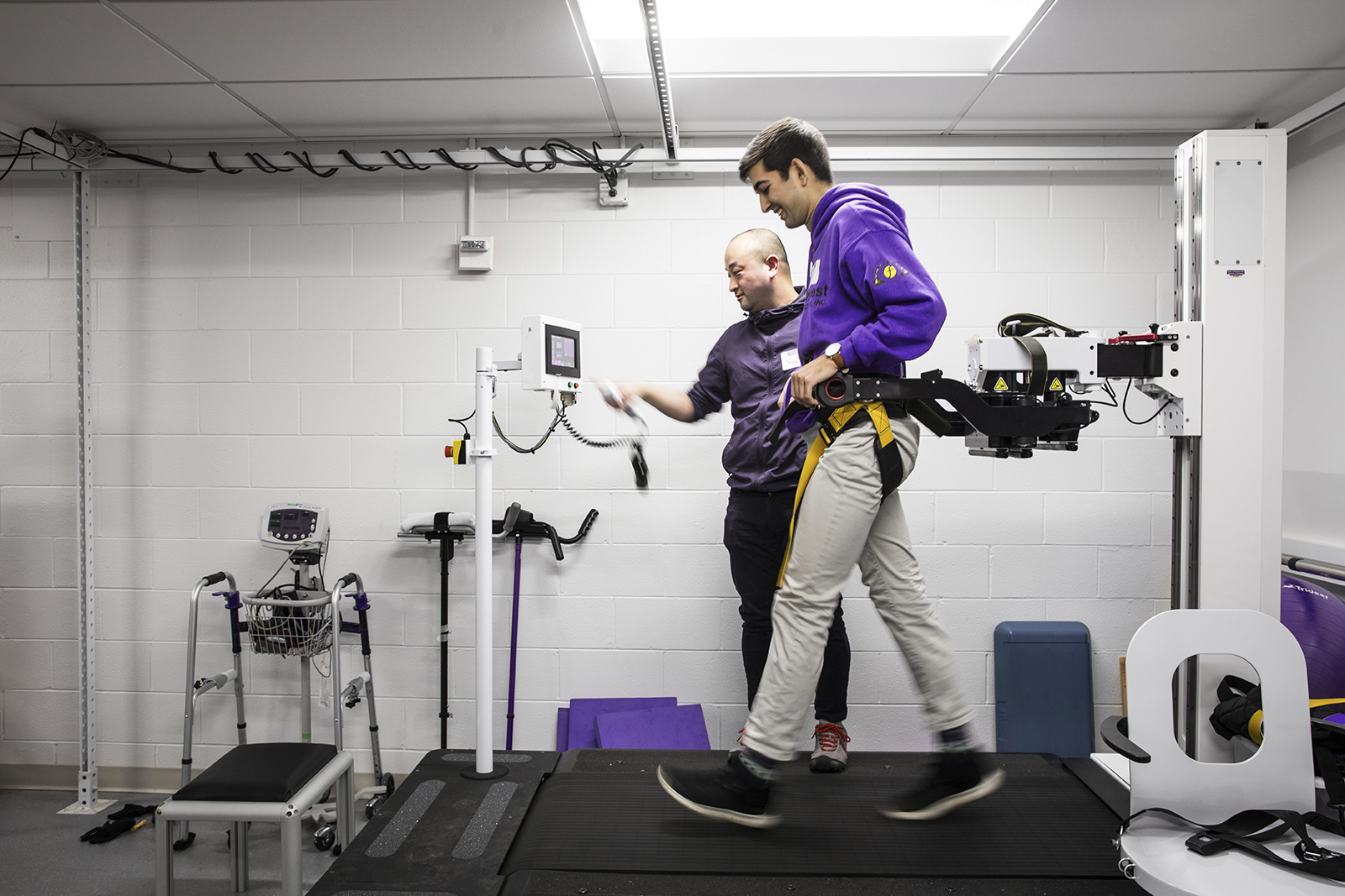 In the Amplifying Movement and Performance (AMP) Lab, Ph.D. student Soshi Samejima works with another student on a KineAssist treadmill for spinal-simulation research. A partnership between the UW's Department of Rehabilitation Medicine and the College of Engineering, the lab advances understanding of both human and robot movement. (Photo by Mark Stone)