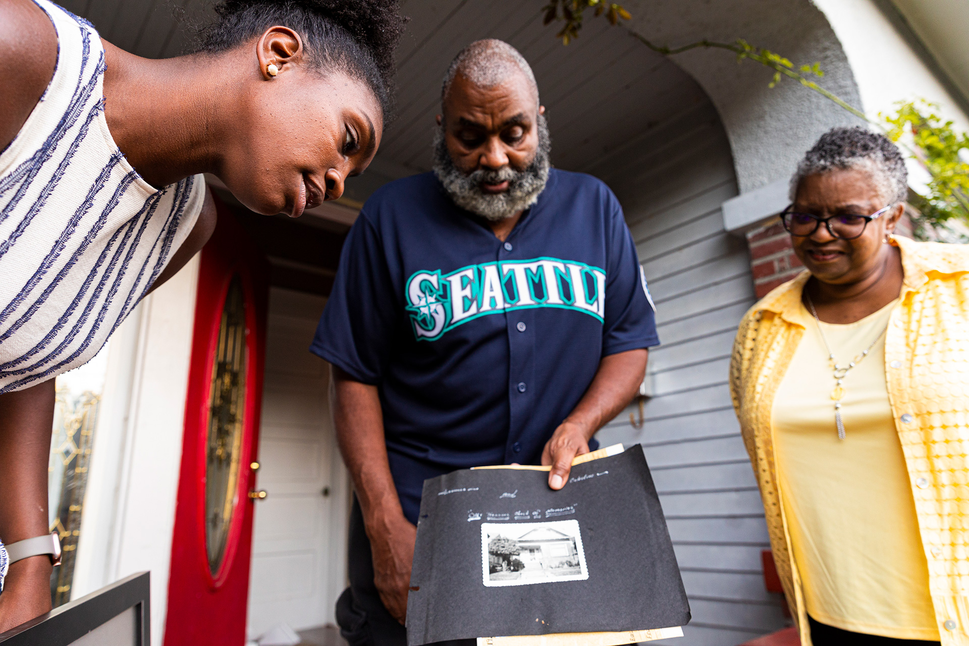 Thomas' parents, Deborah and Gregory Thomas, show a photo of their home from when it was first purchased by Danyelle's paternal grandfather.