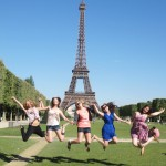 Five Graduate girls jump for joy in front of the Eiffel Tower