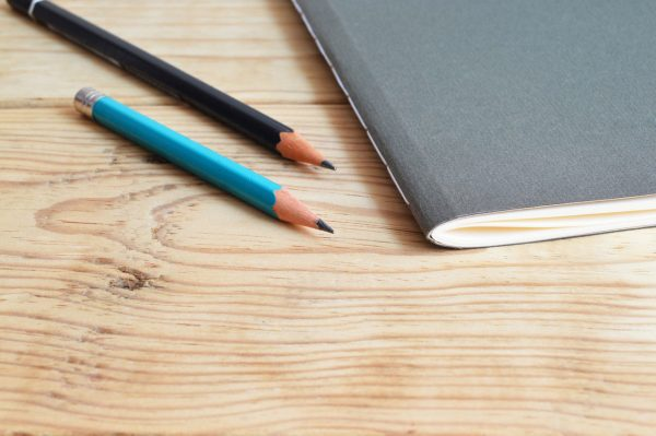 Notebook and pencils on a wood table