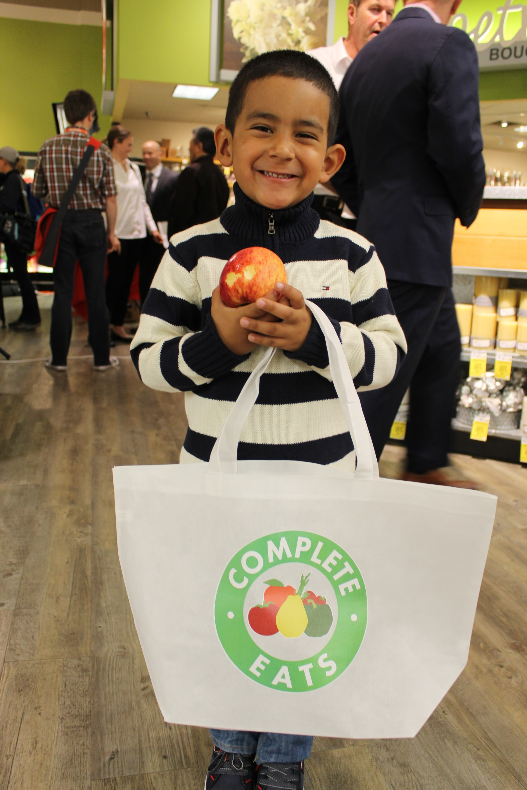 Little boy holding apple and Comple Eats shopping bag.