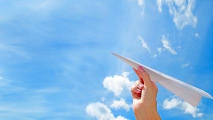 Hombre arrojando avioncito de papel