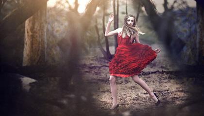 Joven salta en el bosque con vestido rojo